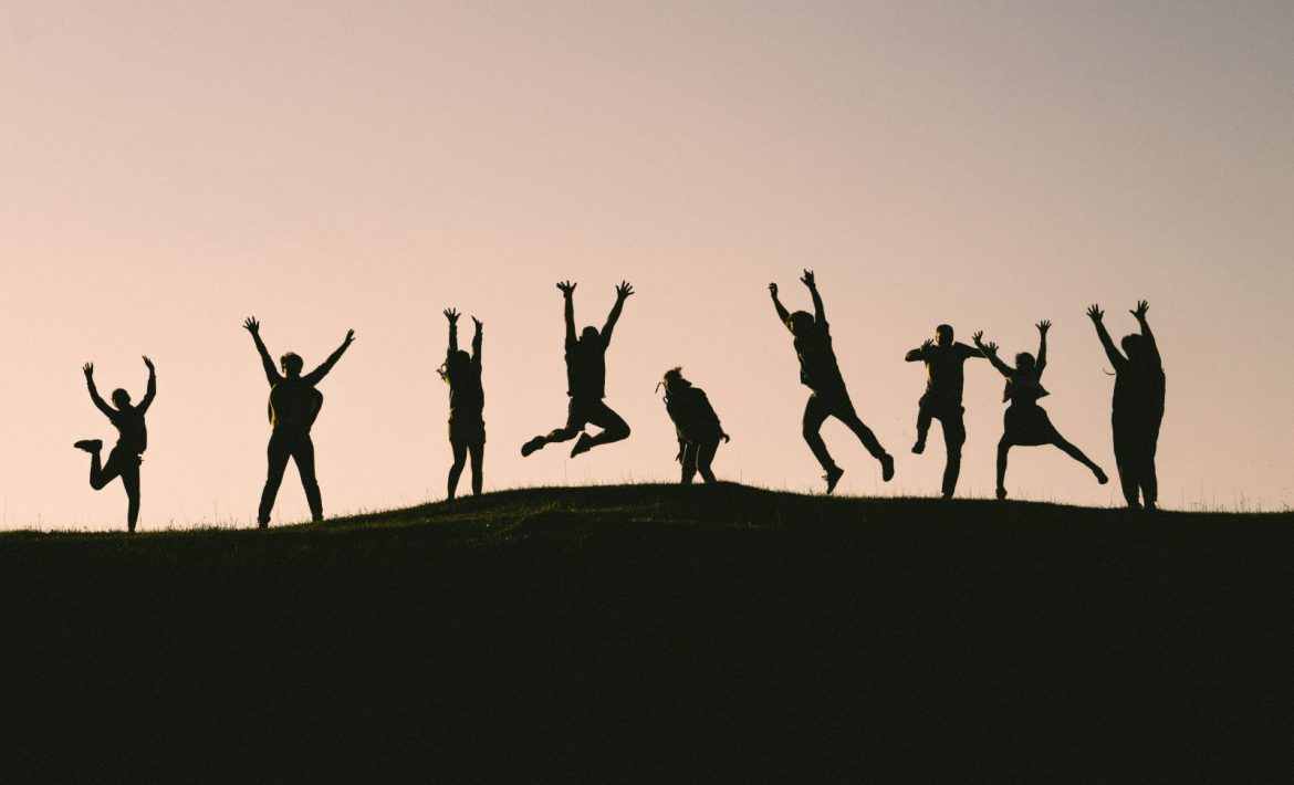 People excitedly jumping on mountain
