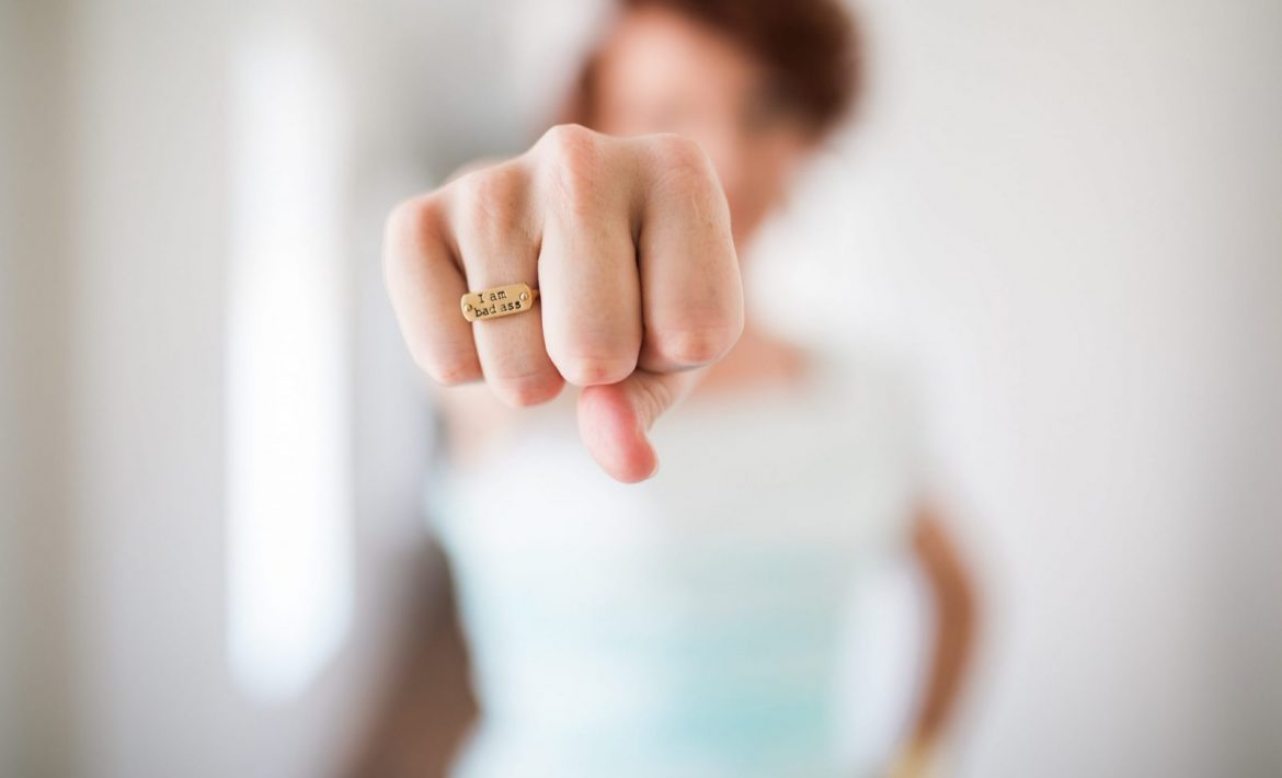 "Woman's fist highlighted with ring that says ""I am a badass"""