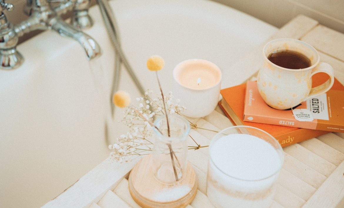 Self-Care - Bathtub with flowers, candles and coffee on the side
