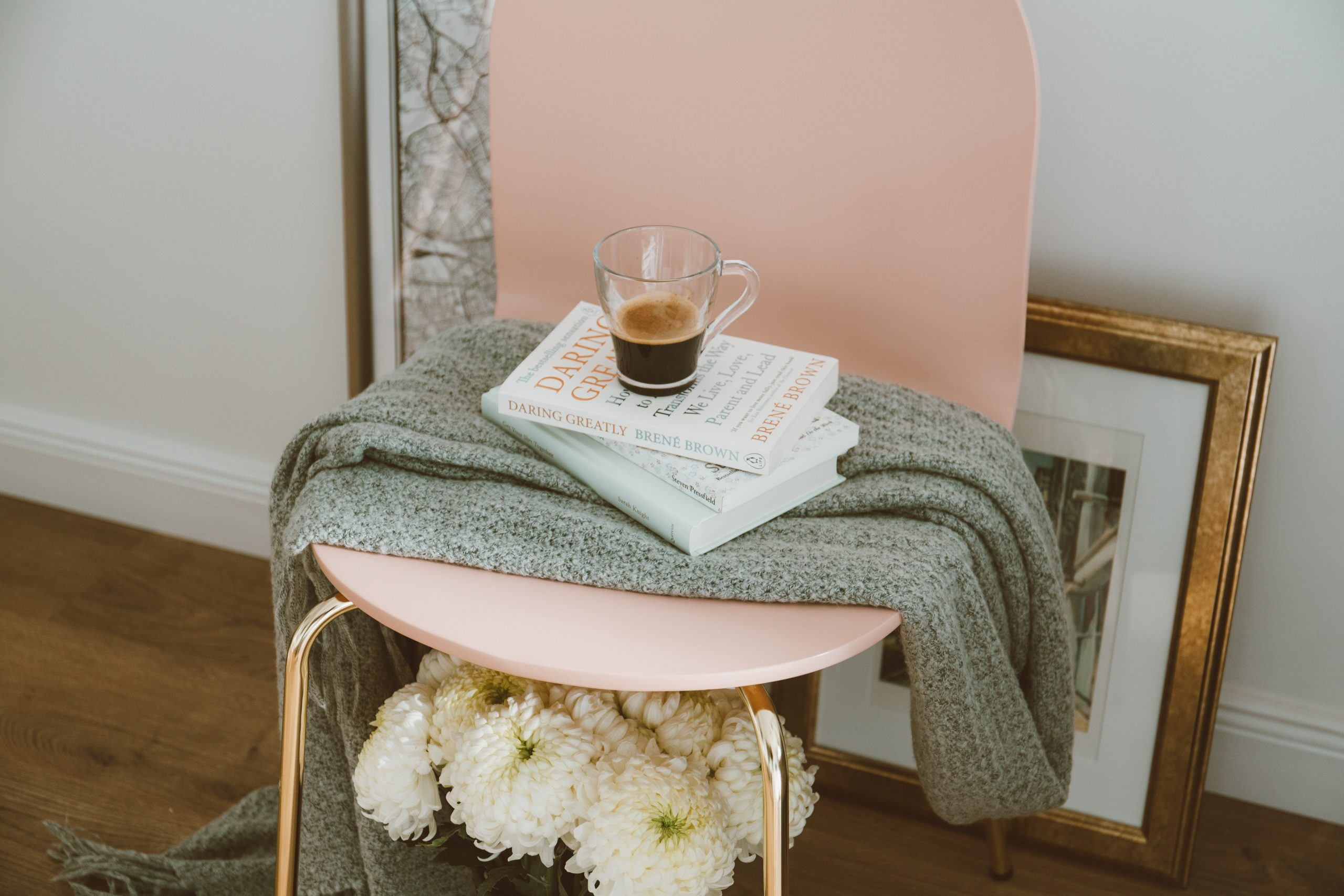 Practice Self-Care: Pink chair with throw, book and cup of coffee.