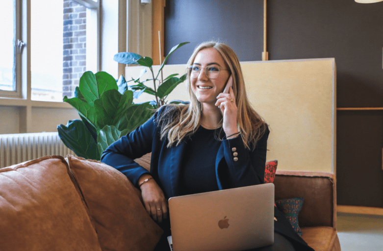 qualified woman sitting on soft while on phone