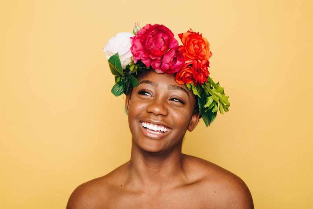 True Selves - Smiling woman wearing a crown of flowers